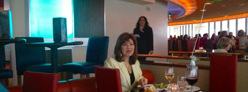 Dark haired woman seated alone at restaurant.